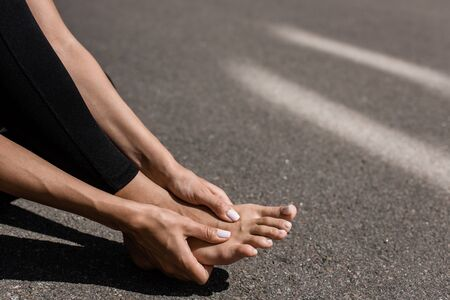 partial view of barefoot sportswoman with foot pain on street Reklamní fotografie