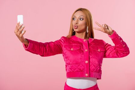 stylish african american woman showing victory gesture and taking selfie isolated on pink, fashion doll concept Stok Fotoğraf