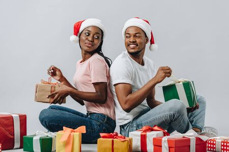 African American couple in Santa hat sitting back to back, opening presents and looking at each other isolated on grey