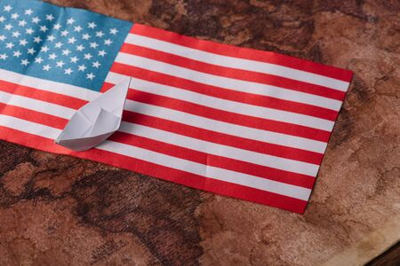white paper boat on ancient world map with American national flag Banque d'images - 132999283