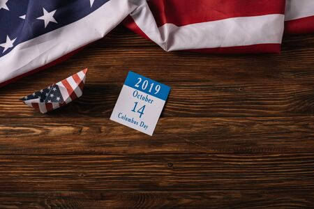 top view of calendar with Columbus Day inscription and paper boat on wooden surface with American national flag Banque d'images - 132968668