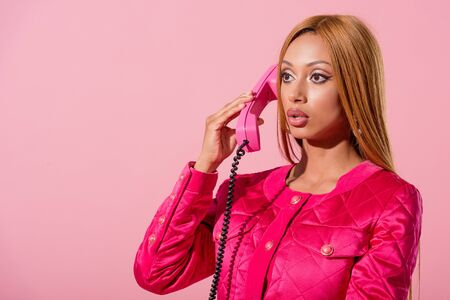 fashionable african american woman talking on retro phone isolated on pink, fashion doll concept Фото со стока