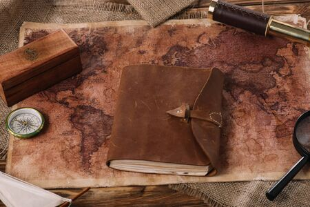 brown leather notebook on wooden table with world map and sacking