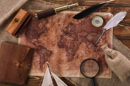 top view of old world map near telescope, nib and compass on wooden surface