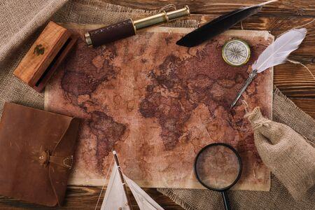 vista dall'alto della mappa del vecchio mondo vicino al telescopio, al pennino e alla bussola su una superficie di legno Archivio Fotografico