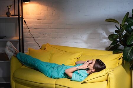 nurse in uniform lying on yellow sofa during night shift
