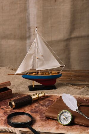 miniature ship, telescope, magnifying glass, leather copy book, compass and nib on old world map and hessian 写真素材