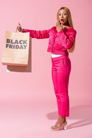 stylish, surprised african american woman holding shopping bag with black friday inscription on pink background, fashion doll concept