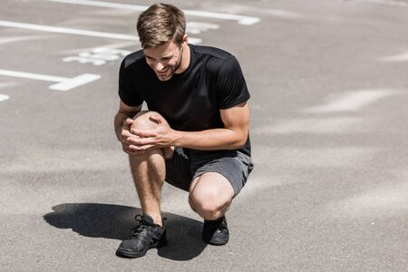 bearded sportsman in black t-shirt with knee pain on street Archivio Fotografico - 132967474