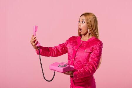 shocked, fashionable african american woman looking at handset isolated on pink, fashion doll concept