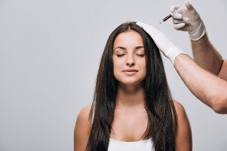 cosmetologist in latex gloves doing scalp mesotherapy to brunette beautiful woman with long hair and closed eyes isolated on grey