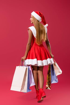 attractive african american girl in santa hat and christmas walking with shopping bags on red background