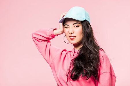 attractive asian woman in pink pullover and cap winking isolated on pink 版權商用圖片