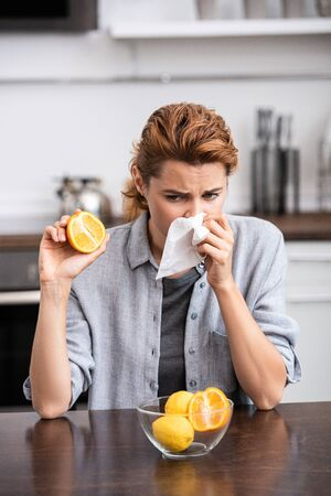 woman with runny nose sneezing in tissue and holding half of tasty orange Stock Photo