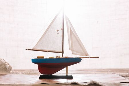 decorative ship with white sail on surface with hessian