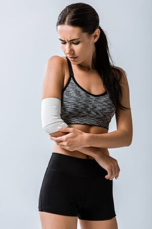 sportswoman with elastic bandage on elbow isolated on grey