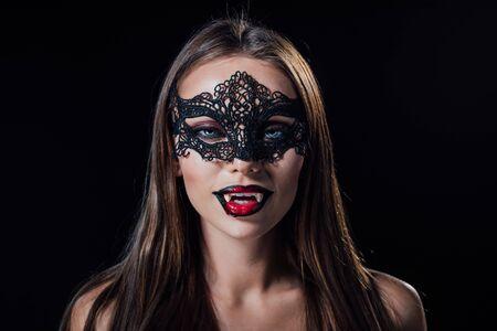 gruseliges Vampirmädchen in Maskerademaske mit Reißzähnen isoliert auf Schwarz