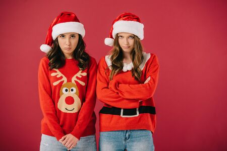 attractive and offended women in sweaters and santa hats looking at camera isolated on red