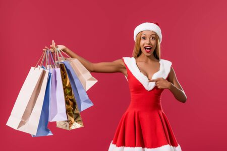 excited african american girl in santa hat and christmas dress pointing with finger at shopping bags isolated on red