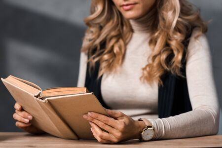 cropped view of  blonde businesswoman sitting at table and reading book in office
