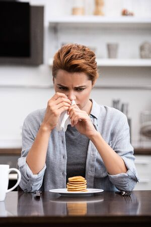 sick woman sneezing in napkin near pancakes at home