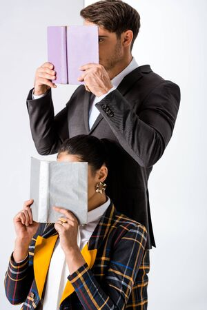stylish man and woman covering faces while holding books on white Stock fotó