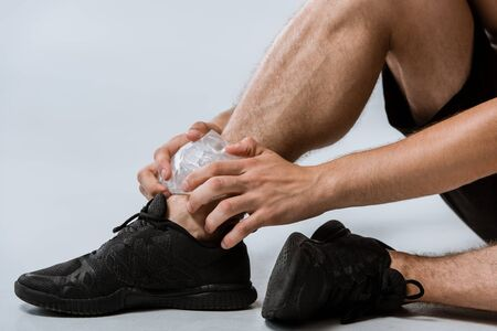 partial view of sportsman in black sneakers using ice for ankle on grey