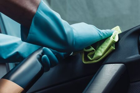 cropped view of car cleaner in rubber gloves cleaning car door Stock Photo