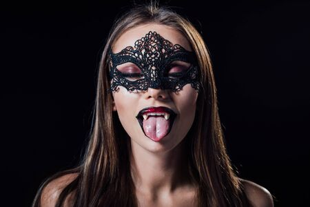 scary vampire girl in masquerade mask with fangs showing fangs isolated on black