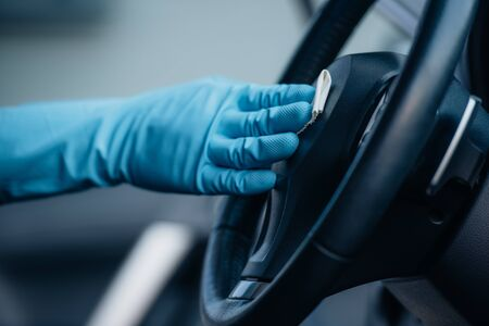 cropped view of car cleaner in rubber glove wiping steering wheel