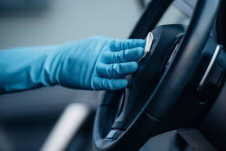 vista ritagliata del detergente per auto nel guanto di gomma che pulisce il volante Archivio Fotografico