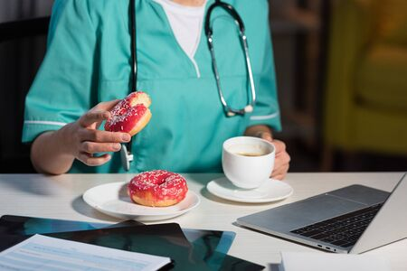 cropped view of of nurse in uniform holding donut and cup during night shift 写真素材