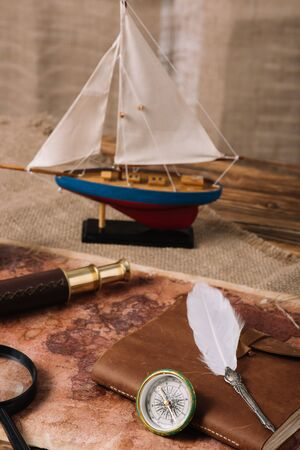 miniature ship, telescope, magnifying glass, leather copy book and nib on old world map and hessian 写真素材