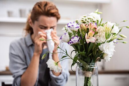 selective focus of bouquet of flowers near woman with pollen allergy sneezing in tissue