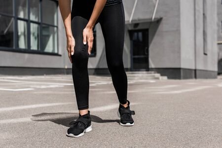 cropped view of sportswoman in black sneakers with knee pain on street