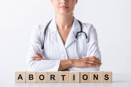 cropped view of doctor with crossed arms near cubes with abortion letters Stockfoto