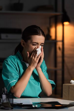 attractive nurse in uniform sneezing and holding napkin during night shift Stock Photo