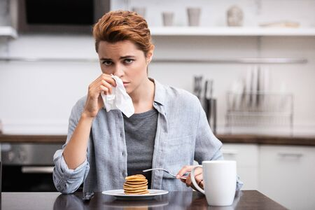sick woman sneezing in tissue near pancakes at home