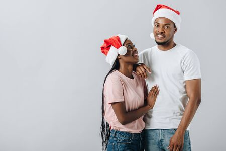 African American couple in Santa hats isolated on grey Stock Photo