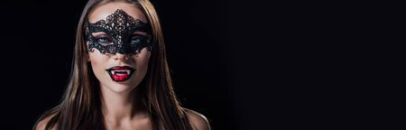 panoramic shot of scary vampire girl in masquerade mask showing fangs isolated on black