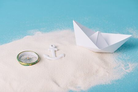 sand with paper boat, compass and anchor on blue background Banque d'images - 132965595