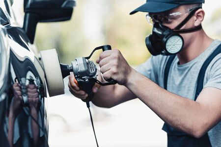 car cleaner in respirator and protective glasses polishing car with polish machine