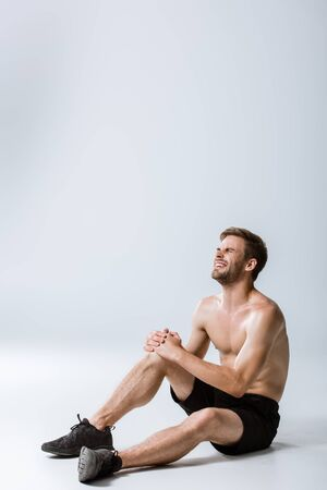 bearded shirtless man with knee pain on grey