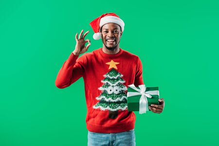 African American man in Christmas sweater and Santa hat showing okay sign and holding gift box isolated on green 免版税图像