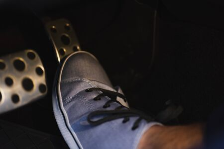 partial view of male leg in sneaker on brakes pedal