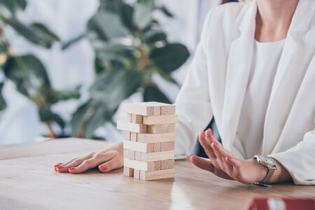 cropped view of risk manager sitting at desk near stacked wooden blocks