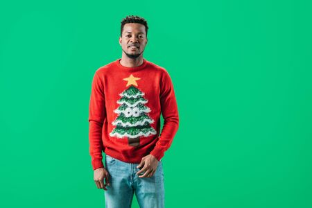 African American man in Christmas sweater looking at camera isolated on green Stock Photo