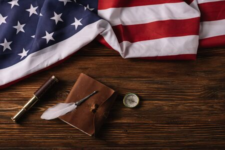 top view of leather notebook, telescope, nib and compass on wooden surface with American national flag