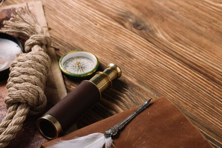 rope cable, nib, compass and telescope on wooden surface Stock fotó
