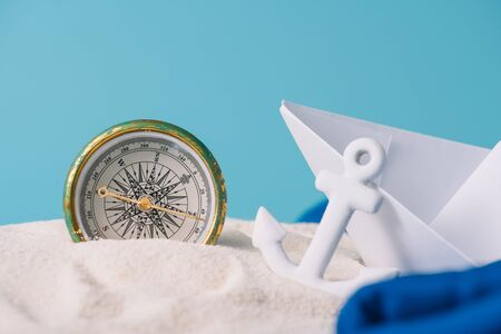 white sand with paper boat, anchor and compass isolated on blue Banque d'images - 132964282